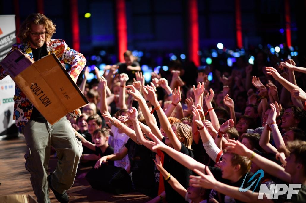 Niels Favrskov deler giveaway præmier ud til publikum fra en scene