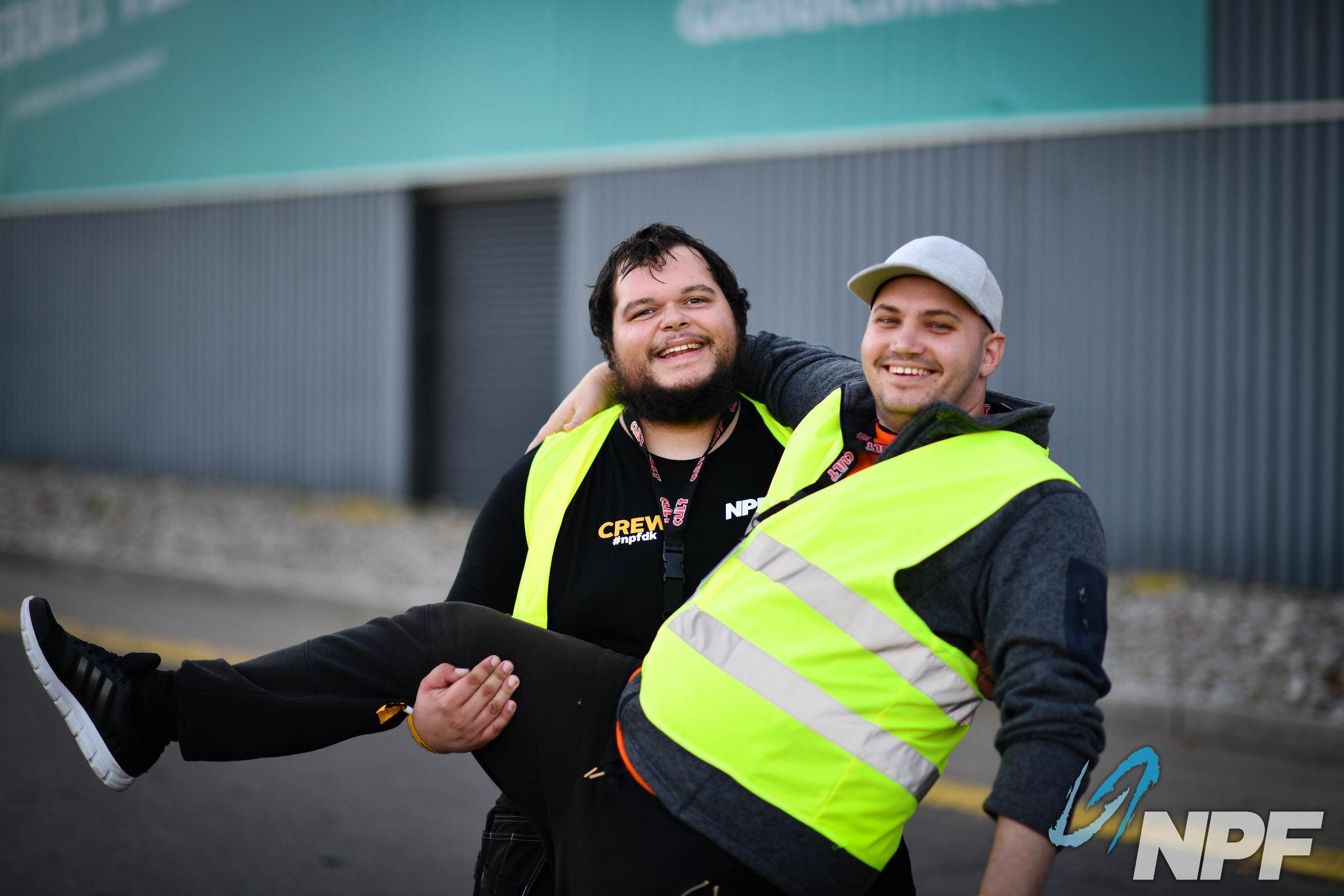 To glade crew der posere foran kamera. Den ene holder den eneste ben oppe og smiler